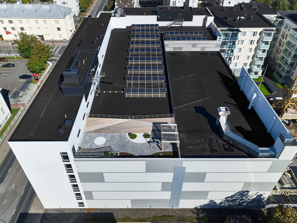 Aerial view of the brand new apartment building with solar panels on the roof.