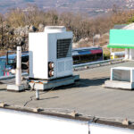 Air conditioning system assembled on top of a building. Air vents on top of commercial building. Air cooled water chillers top of roof. Outdoor climate unit and cooling and heating systems.