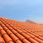 Red tile roof under blue sky. The photo is divided in half. One part is a roof made of clay tiles and the other is a pure blue sky.