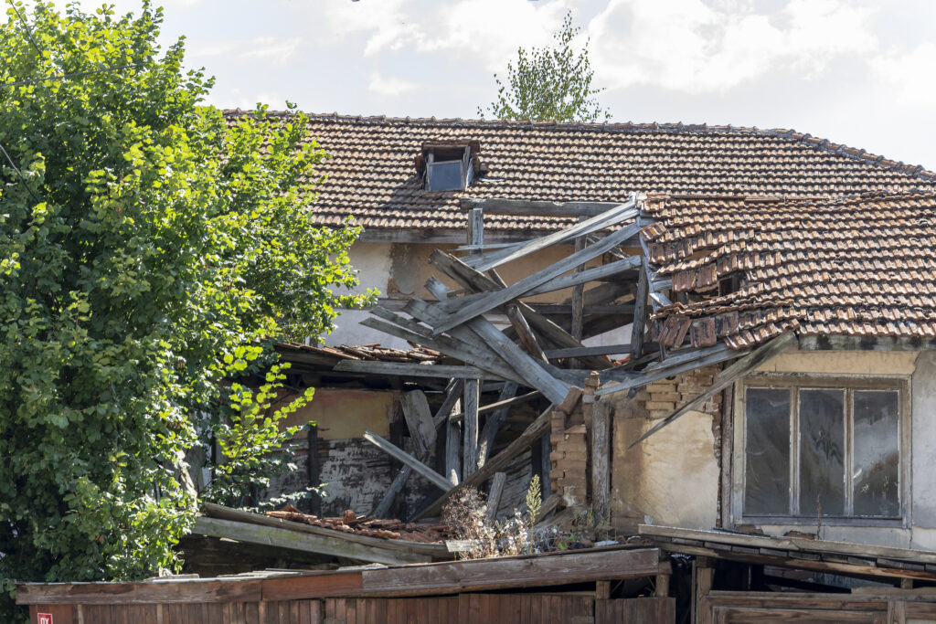 collapsed roof of a old house, wooden roof with tiles collapsed.